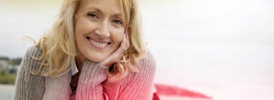 Venstrecentreret billede af en midaldrende kvinder, der smiler.W