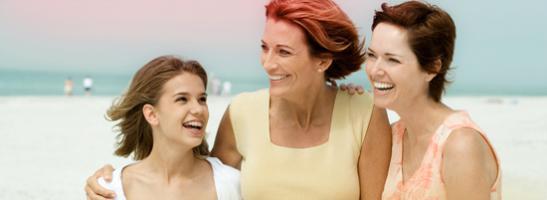 Billede af tre kvinde, der holder om hinanden, en yngre kvinde til venstre og to ældre kvinder til højre.