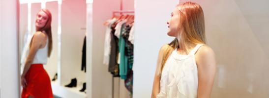 Billede af en pige, der står foran et spejl og prøver tøj.