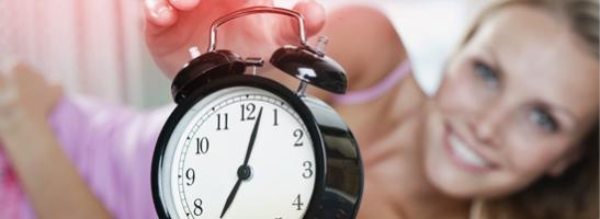 Billede af et vækkeur med en kvinde i baggrunden, der strækker sig for at slukke alarmen.