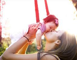 Billede af en kvinde som holder og kysser en baby.W