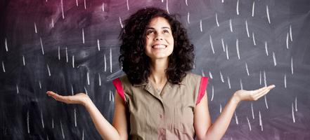 Billede af en ung kvinde stående foran en tavle.