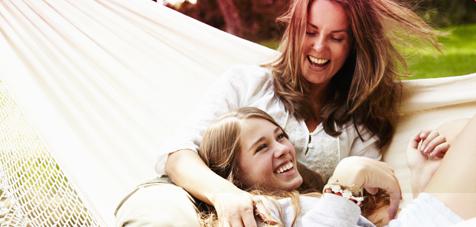 Billede af to smilende kvinder liggende i en hængekøje.