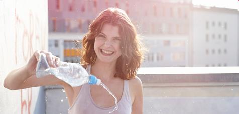 Billede af en ung smilende kvinde, som står med en vandflaske i hånden og sprøjter vand.
