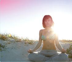 Billede af en kvinde der sidder på stranden og mediterer. Billedet illustrerer, at det er muligt at slappe af og leve normalt selv når du har menstruation.