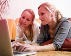 Billede af mor og datter siddende foran en computer. Billedet illustrerer hvordan en mor hjælper sin datter med at finde oplysninger om den første menstruation på nettet.