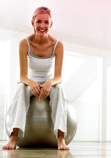 Billede af en kvinde i træningstøj, der sidder på en gymnastikbold. Billedet illustrerer, at der er muligt at motionere og træne mens du har menstruation.