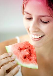 Billede af en ung kvinde, der spiser vandmelon. Billedet illustrerer et af de tips til at lindre menstruationssmerter – spise frugt eller grøntsager med højt vandindhold.