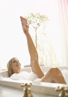 Billede af en kvinde i et badekar med benene i vejret. Billedet illustrerer, at det er muligt at slappe af og leve som sædvanligt, selvom du har menstruation.